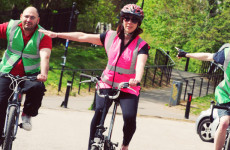 Three cyclists wearing high visibility vests signalling right