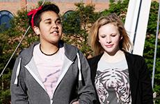 Two girls walking arm in arm