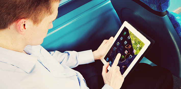 Person using tablet computer on a bus