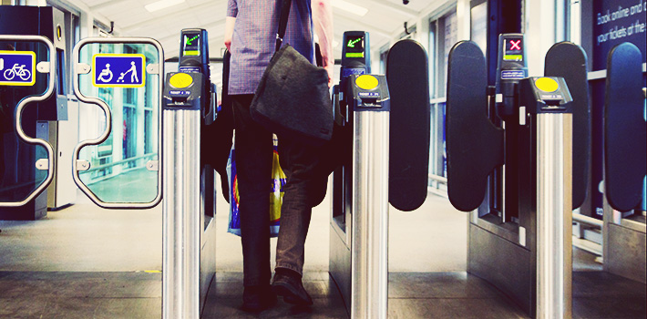 Person passing through ticket barriers at train station