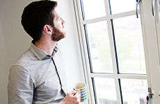 Man drinking coffee and looking out of the window