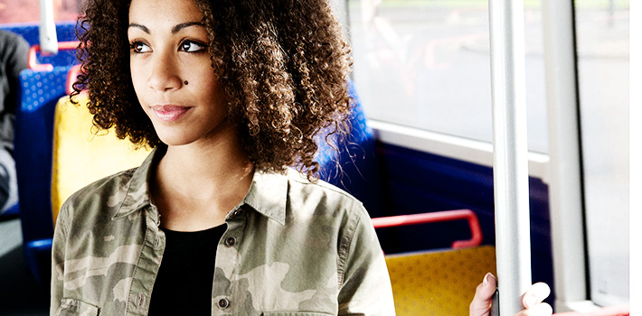 Young woman standing on bus