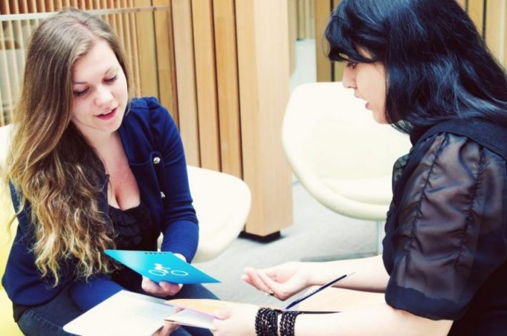 Two women discussing Connected business materials