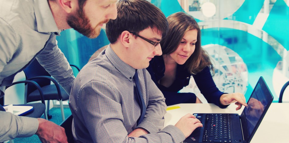 Three people looking at a laptop in a meeting