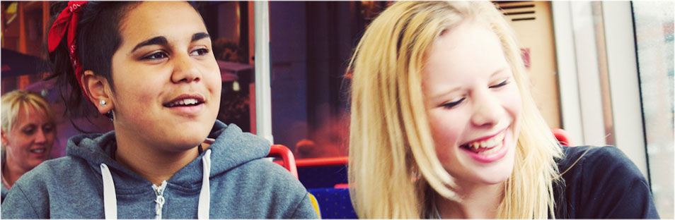 Two young people laughing on the bus