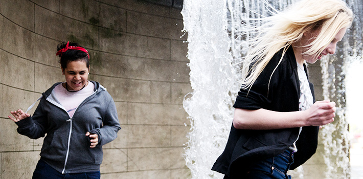 Two young people running through the waterfall fountain