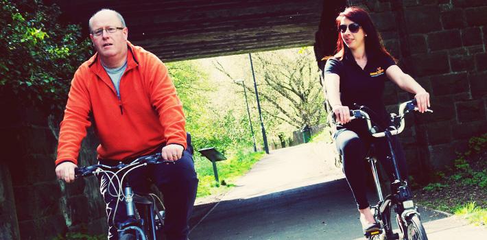 A couple cycling through the park
