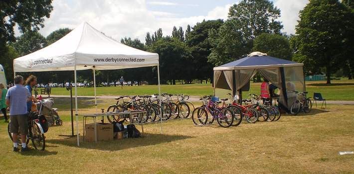 Two gazebos in a park with bikes stood up beneath them