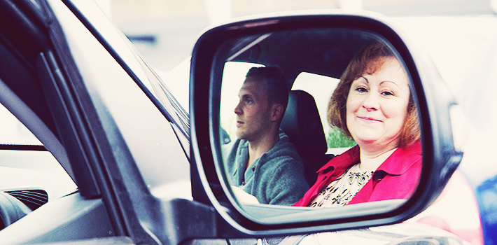 Couple reflected in car wing mirror