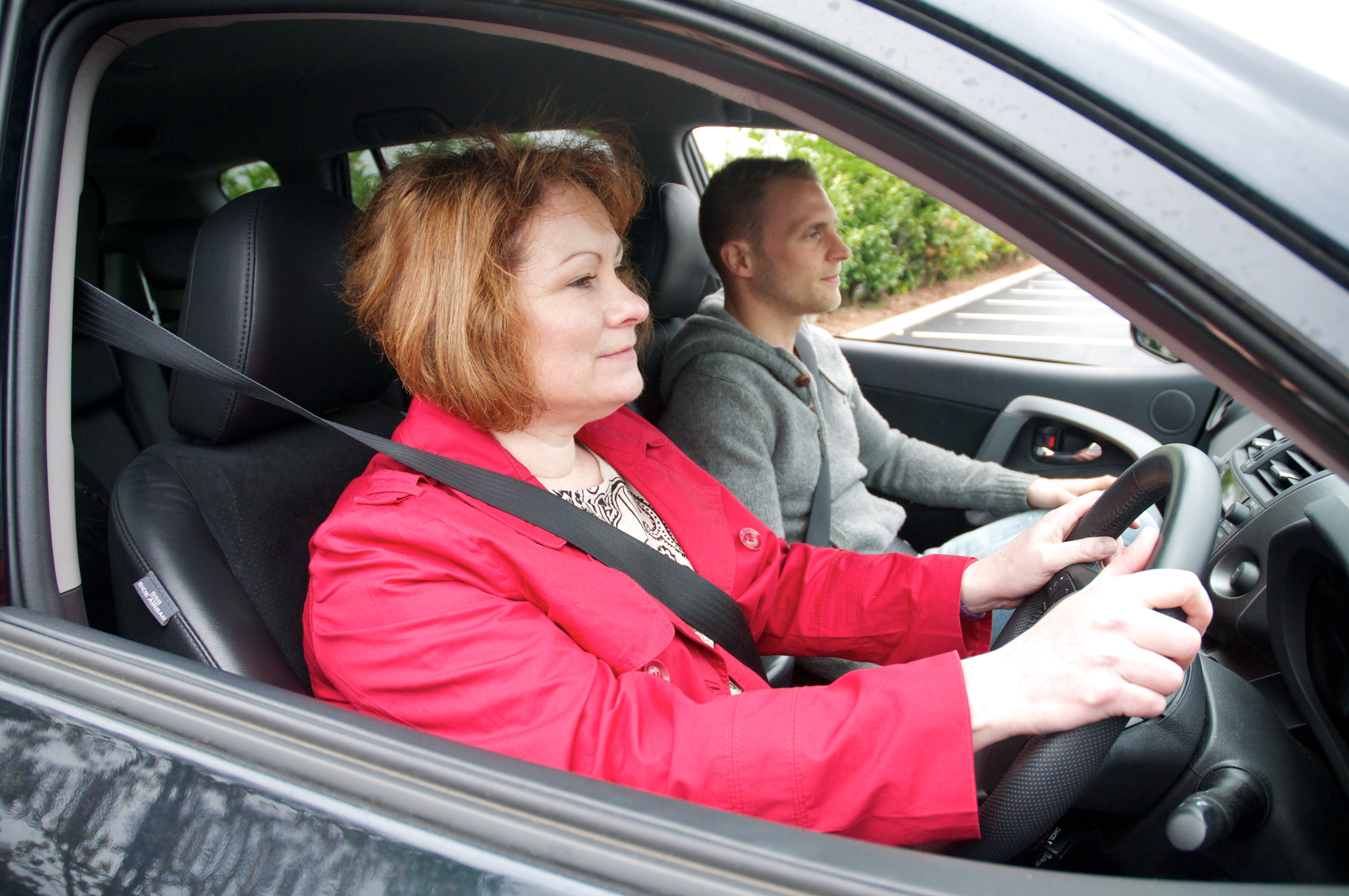 Female in red jacket driving car with male passenger